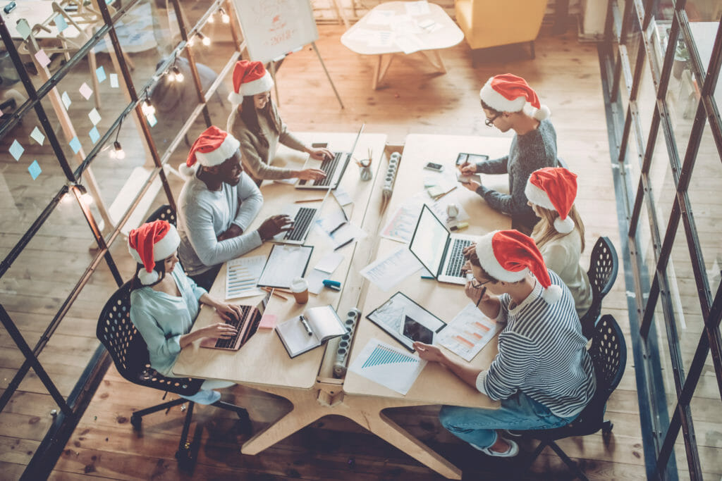 Group of young business people working in Santa hats.