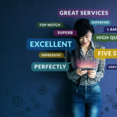 Soft focus of Happy Client standing at the Wall, Smiling while using Smartphone. Surrounded by Positive Review in Speech Bubble and Social Network icons.