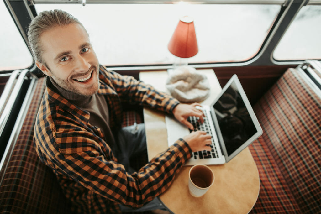Portrait of smiling bearded young man working on visual content on laptop with cup of coffee on table